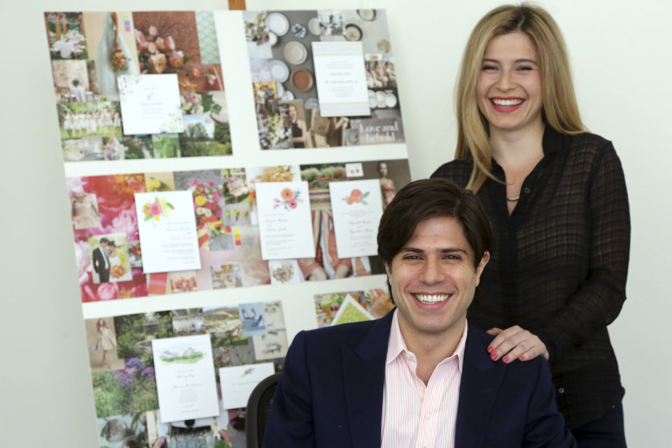 In this Friday, March 29, 2013 photo Alexa Hirschfeld, right, and James Hirschfeld smile as they pose for a photo at their office in New York. Paperless Post has defied its original digital business model successfully once. Now the online invitation and greeting card startup is taking that defiance a step further. The New Yaork company launched PAPER by Paperless Post in October after customers requested a way to get its electronic greeting cards and invitations in a more old-fashioned way: On actual paper. Now Paperless Post is teaming up with stationery. (AP Photo/Mary Altaffer)