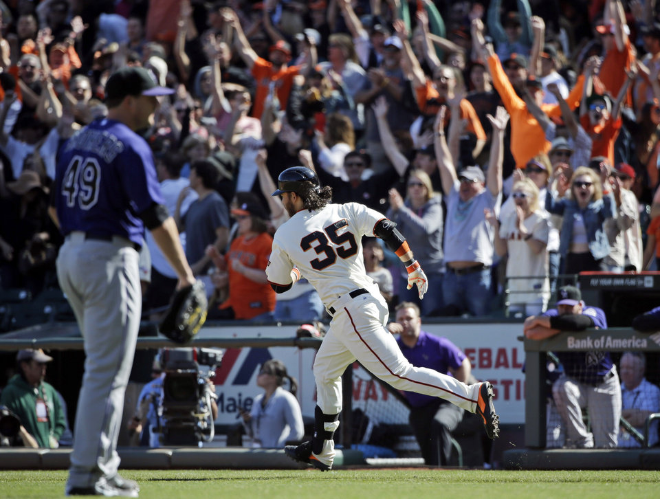 Photo - San Francisco Giants' Brandon Crawford runs down the first base line during his walk-off home run off Colorado Rockies relief pitcher Rex Brothers, left, during the 10th inning of a baseball game on Sunday, April 13, 2014, in San Francisco. San Francisco won 5-4. (AP Photo/Marcio Jose Sanchez)