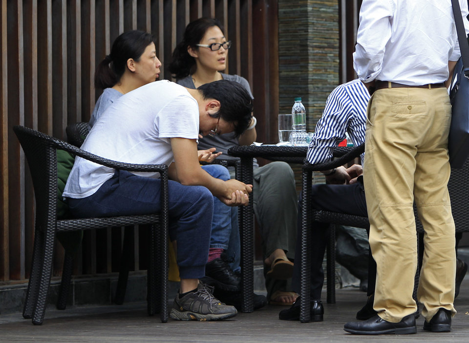 Photo - A Chinese relative, in a T-shirt, of passengers aboard a missing Malaysia Airlines plane, looks down as he sits outside a cafe at a resort in Cyberjaya, Malaysia, Thursday, March 20, 2014. Flight 370 disappeared March 8 on a night flight from Kuala Lumpur to Beijing. Malaysian authorities have not ruled out any possible explanation, but have said the evidence so far suggests the flight was deliberately turned back across Malaysia to the Strait of Malacca, with its communications systems disabled. (AP Photo/Lai Seng Sin)