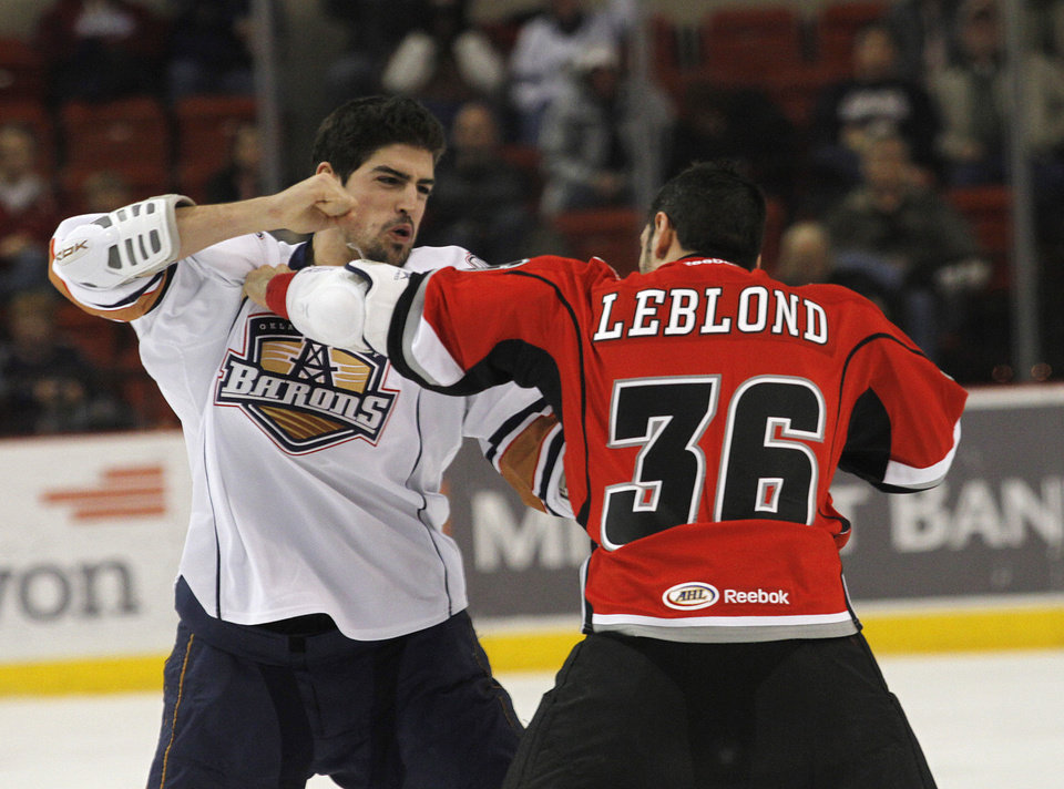 Photo - OKC's Cameron Abney (40) and Abbotsford's Pierre-Luc Letourneau-Leblond (36) fight during a game between the Oklahoma City Barons and the Abbotsford Heat in Oklahoma City, Sunday, Jan. 15, 2012.  Photo by Garett Fisbeck, For The Oklahoman