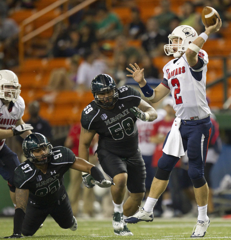 Photo - Hawaii defensive lineman Tavita Woodard (97) and defensive lineman Siasau Matagiese (59) rush South Alabama quarterback Ross Metheny (2) in the third quarter of an NCAA college football game Saturday, Dec. 1, 2012, in Honolulu. (AP Photo/Eugene Tanner)