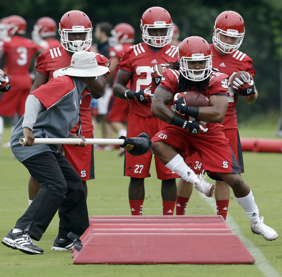 Photo - North Carolina State running back Tony Creecy (26) runs through a drill during the team's first NCAA college football practice of the season in Raleigh, N.C., Saturday, Aug. 2, 2014. (AP Photo/Gerry Broome)