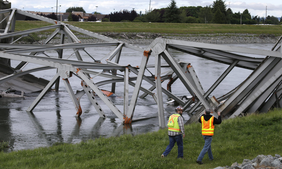Photo - Workers walk past the collapsed portion of the Interstate 5 bridge at the Skagit River Friday, May 24, 2013, in Mount Vernon, Wash. A truck carrying an oversize load struck the four-lane bridge on the major thoroughfare between Seattle and Canada, sending a section of the span and two vehicles into the Skagit River below Thursday evening. All three occupants suffered only minor injuries.  (AP Photo/Elaine Thompson)