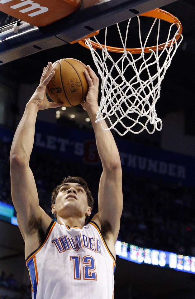 Photo - Oklahoma City's Steven Adams (12) goes up for a dunk during the NBA game between the Oklahoma City Thunder and the Minnesota Timberwolves at the Chesapeake Energy Arena, Sunday, Dec. 1, 2013. Photo by Sarah Phipps, The Oklahoman