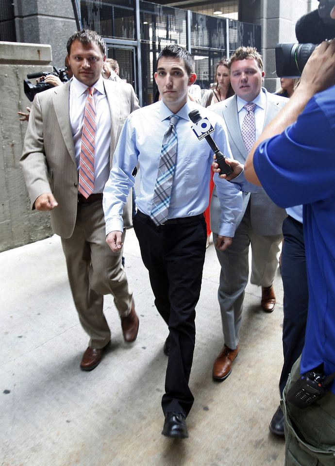 After confessing on video to killing a man in a drunk-driving accident, Matthew Cordle, 22, with his lawyers Martin Midian, left, and George Breitmayer, surrenders to sheriff's deputies at the Franklin County Corrections Center in Columbus, Ohio, Monday, Sept. 9, 2013. (AP Photo/The Columbus Dispatch, Adam Cairns)