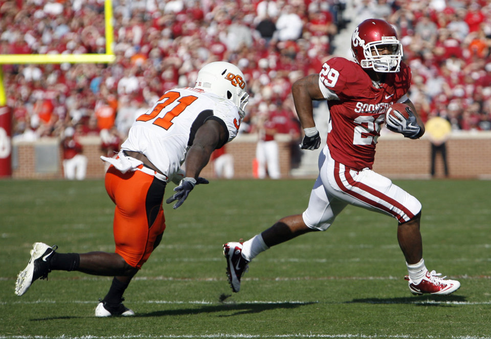 Photo - OU's Chris Brown (29) rushes as OSU's Lucien  Antoine (31) during the first half of the Bedlam college football game between the University of Oklahoma Sooners (OU) and the Oklahoma State University Cowboys (OSU) at the Gaylord Family-Oklahoma Memorial Stadium on Saturday, Nov. 28, 2009, in Norman, Okla. Photo by Sarah Phipps, The Oklahoman