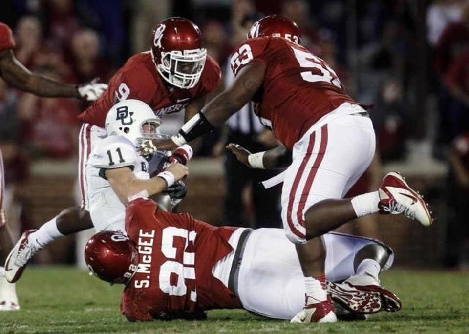 Baylor quarterback Nick Florence (11) is brought down by Oklahoma defensive back Gabe Lynn (9), defensive tackle Stacy McGee (92) and defensive tackle Casey Walker (53) in the fourth quarter of an NCAA college football game in Norman, Okla., Saturday, Nov. 10, 2012. Oklahoma won 42-34. (AP Photo/Sue Ogrocki)