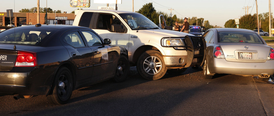 An Oklahoma Highway Patrol car rammed this stolen white pickup Thursday after the driver led officers on a chase and also hit the silver car at SW 119 Street and Western Avenue in Oklahoma City Thursday. Photo by Paul B. Southerland, The Oklahoman  <strong>PAUL B. SOUTHERLAND - PAUL B. SOUTHERLAND</strong>