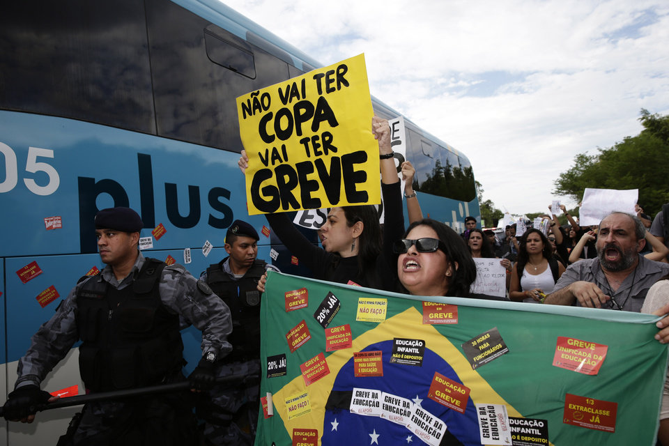 Photo - Protesters hold banners and shout next to the bus carrying some members of Brazil's national soccer team as it departs for the Granja Comary training center, where the team will stay during the World Cup, as riot police try to keep demonstrators away from the bus departing a hotel at the Antonio Carlos Jobim International Airport in Rio de Janeiro, Brazil, Monday, May 26, 2014. Demonstrators protested against the money being spent by the local government on the World Cup. The sign reads in Portuguese