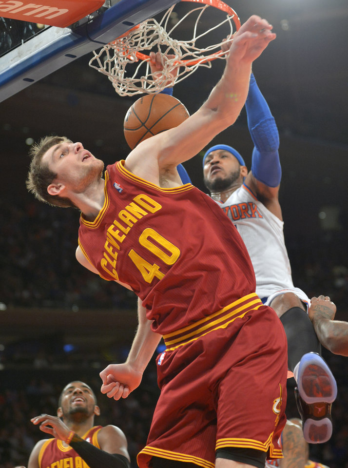 Photo - New York Knicks' Carmelo Anthony dunks the ball over Cleveland Cavaliers' Tyler Zeller (40) during the first quarter of an NBA basketball game Thursday, Jan. 30, 2014, at Madison Square Garden in New York. (AP Photo/Bill Kostroun)