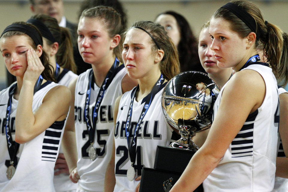 Photo - With their runner-up trophy, Cordell players watch as the Preston team receive their medals and championship trophy at the end of the Class 2A Girls State Championship game between Preston and Cordell at Jim Norick Arena at State Fair Park  on Saturday, Mar. 15, 2014.  Preston won,  45-41. Photo by Jim Beckel, The Oklahoman