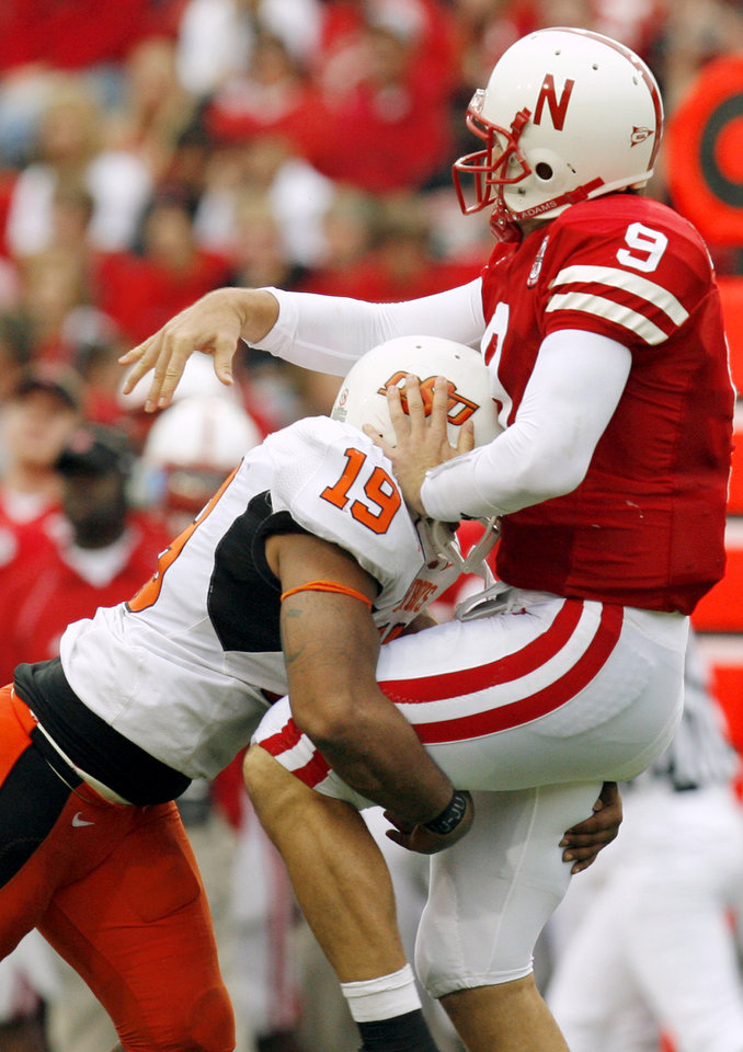Photo - Nebraska quarterback Sam Keller (9) gets off a pass under heavy pressure from OSU's Jeremy Nethon (19) during the college football game between Oklahoma State University (OSU) and the University of Nebraska (NU) at Memorial Stadium in Lincoln, Neb., Saturday, October 13, 2007. OSU won, 45-14. By Nate Billings, The Oklahoman  ORG XMIT: KOD