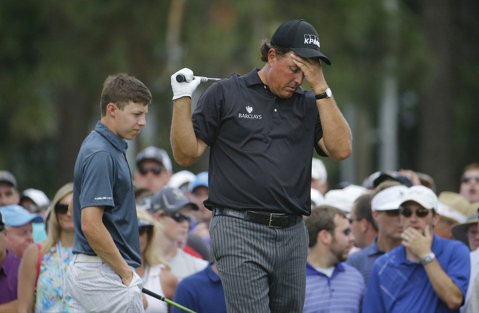 Photo - Phil Mickelson, right, reacts to his tee shot on the eighth hole as Amateur, Matthew Fitzpatrick, England, elks by during the first round of the U.S. Open golf tournament in Pinehurst, N.C., Thursday, June 12, 2014. (AP Photo/Matt York)