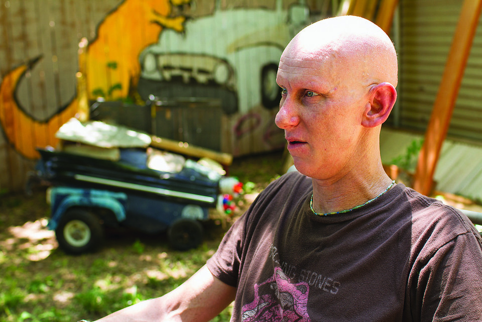 Photo - Josh Cockle sits with a piece of his art in the background in his backyard in the Paseo Arts District. The artwork was created entirely from rubble scattered by the May 20 tornado in Moore and will be sold in an art fundraiser to benefit Moore Public Schools. PHOTO BY CHRIS JAMES, The Oklahoman  Chris James