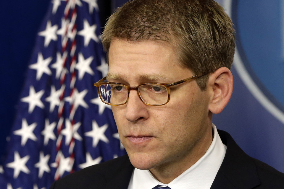 Photo - White House press secretary Jay Carney listens to a follow up question regarding the school shooting in Newtown, Conn., after he told reporters that President Barack Obama is receiving updates on the situation, Friday, Dec. 14, 2012, during the daily press briefing at the White House in Washington. (AP Photo/Charles Dharapak)