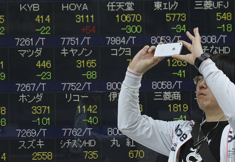 Photo - A man takes a photo with his smartphone camera in front of an electronic stock board of a securities firm in Tokyo, Wednesday, May 7, 2014. A dismal day on Wall Street spilled over into Asian trading Wednesday as jitters over the valuations of technology companies contributed to a sharp drop in Japan's benchmark. The Nikkei 225 stock index fell 2.3 percent to 14,120.25. Japanese markets were closed the previous two days for public holidays. (AP Photo/Eugene Hoshiko)