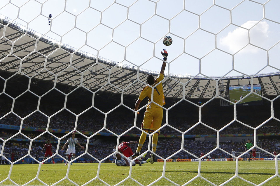 Photo - Argentina's goalkeeper Sergio Romero deflects a header by Iran's Ashkan Dejagah over the goal during the group F World Cup soccer match between Argentina and Iran at the Mineirao Stadium in Belo Horizonte, Brazil, Saturday, June 21, 2014. (AP Photo/Fernando Vergara)