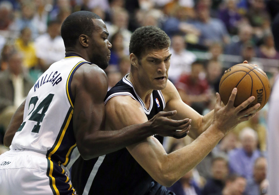 Brooklyn Nets' Brook Lopez, right, drives on Utah Jazz's Paul Millsap during the first half of an NBA basketball game, Saturday, March 30, 2013, in Salt Lake City. (AP Photo/George Frey)