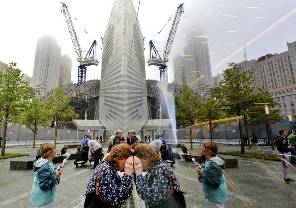 Photo - People try to look through the windows of the National September 11 Memorial Museum during the museum's dedication in New York, on Thursday, May 15, 2014. (AP Photo/Justin Lane, Pool)