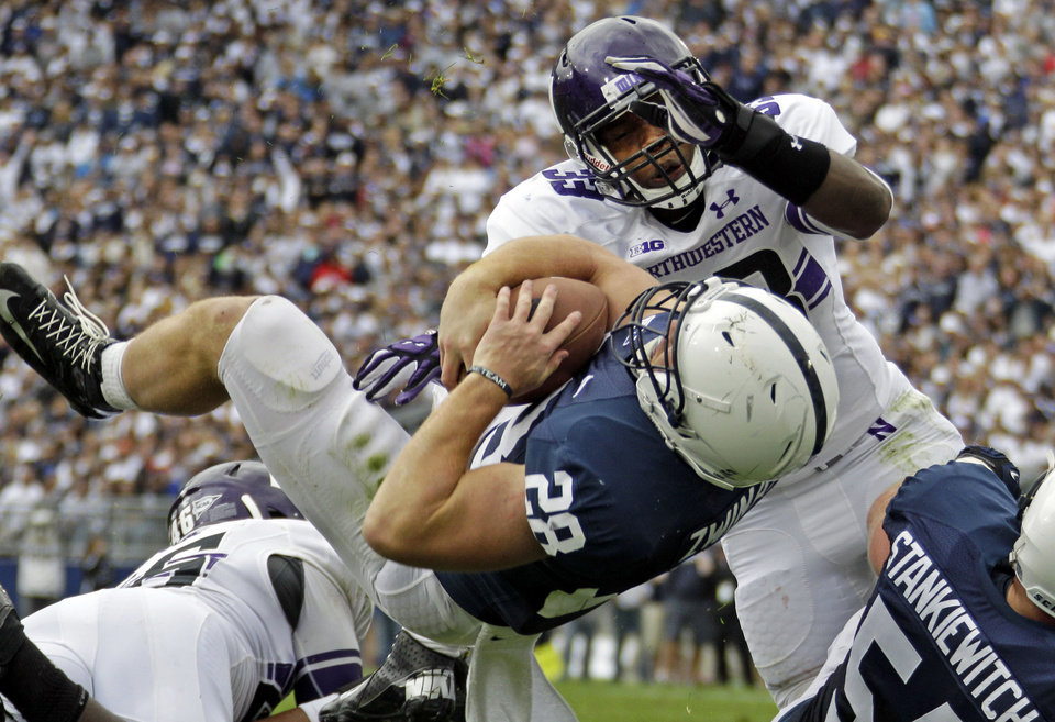 Penn State running back Zach Zwinak (28) dives into the end zone past Northwestern linebacker David Nwabuisi (33) for a second quarter touchdown during an NCAA football game in State College, Pa., Saturday, Oct. 6, 2012. (AP Photo/Gene J. Puskar)