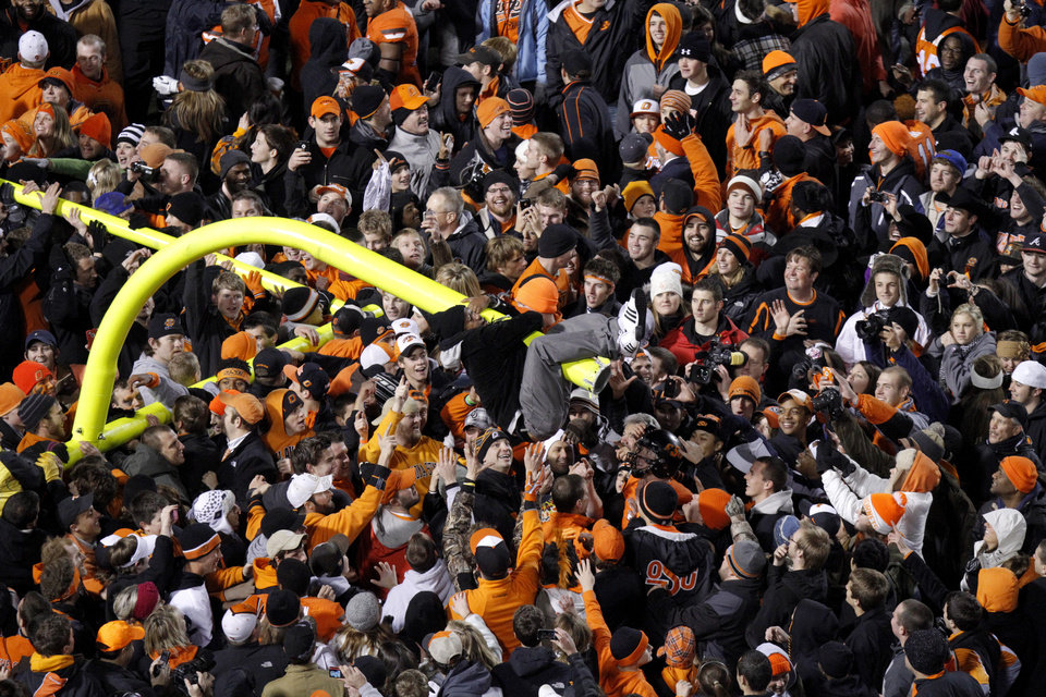 Photo - Oklahoma State fans celebrate following the Bedlam college football game between the Oklahoma State University Cowboys (OSU) and the University of Oklahoma Sooners (OU) at Boone Pickens Stadium in Stillwater, Okla., Saturday, Dec. 3, 2011. Photo by Bryan Terry, The Oklahoman