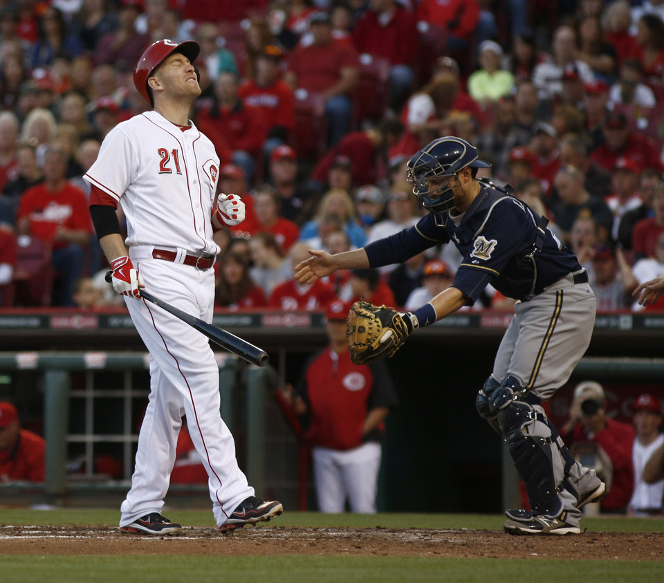 Photo - Cincinnati Reds' Todd Frazier (21) reacts after being hit by a pitch from Milwaukee Brewers starting pitcher Yovani Gallardo in the fourth inning of a baseball game, Saturday, May 3, 2014, in Cincinnati. Brewers catcher Jonathan Lucroy is at right.  (AP Photo/David Kohl)