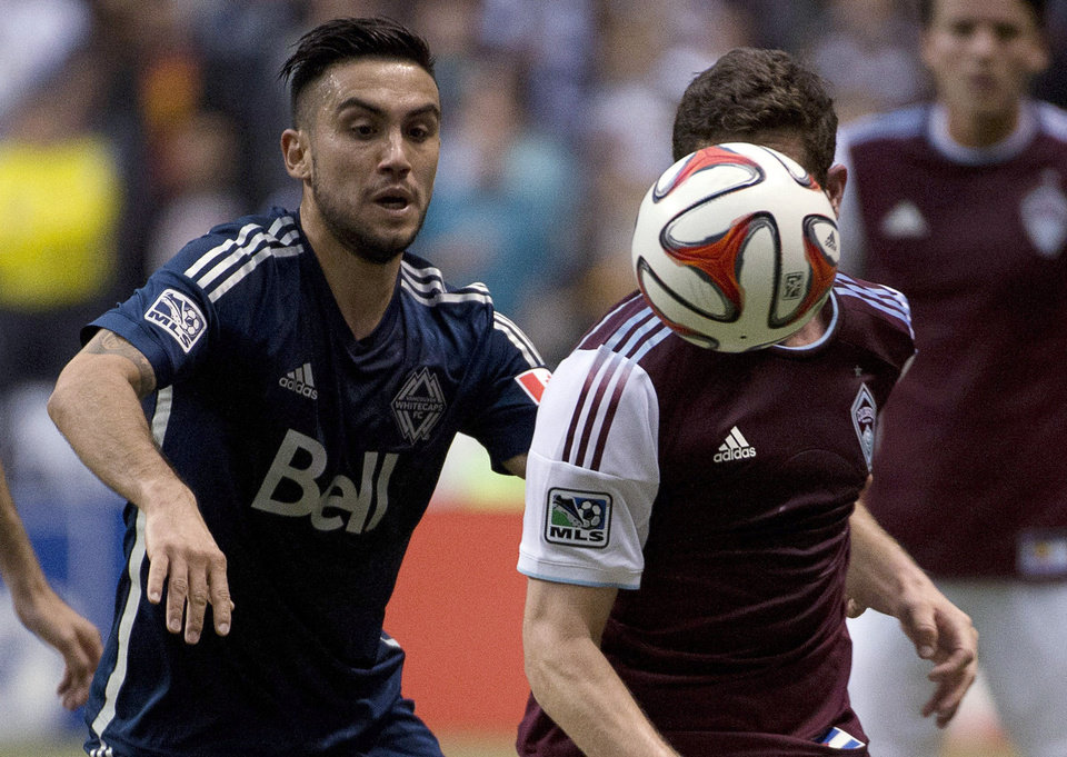 Photo - Vancouver Whitecaps FC's Pedro Morales fights for control of the ball with Colorado Rapids FC's Dillon Powers during second half of MLS soccer action in Vancouver, Canada, Saturday, April 5, 2014. (AP Photo/The Canadian Press, Jonathan Hayward)