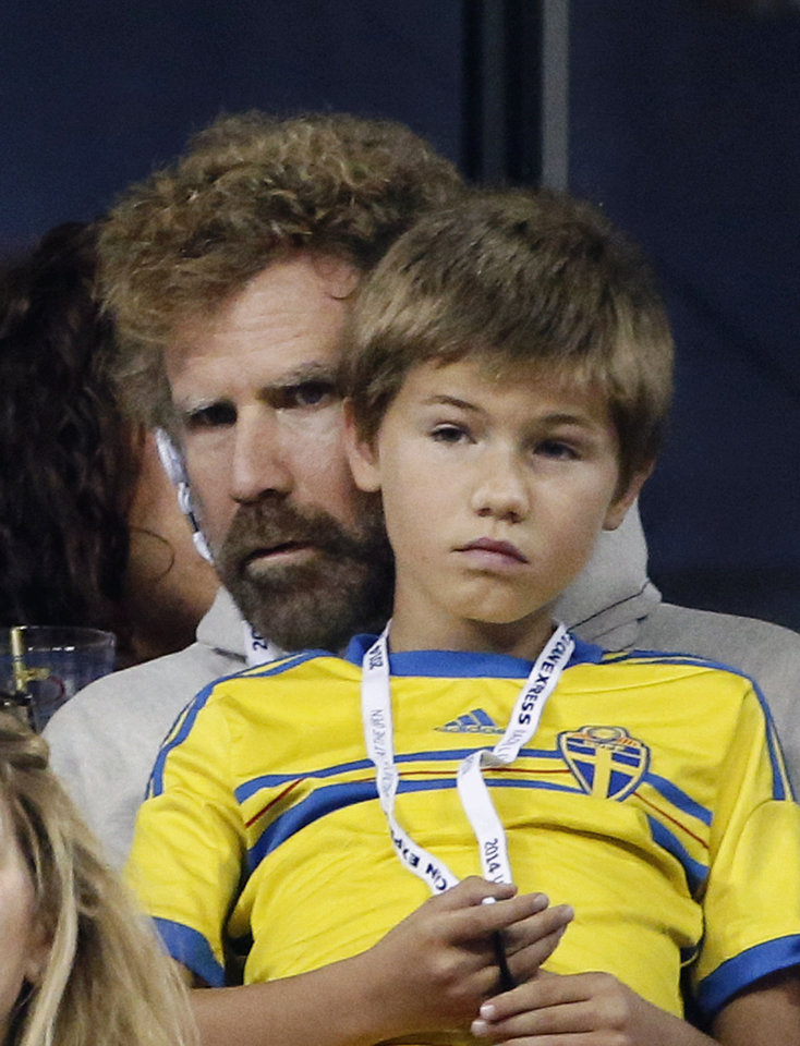 Photo - Actor Will Ferrell and his son Mattias watch a match between Roger Federer, of Switzerland, and Sam Groth, of Australia, during the second round of the U.S. Open tennis tournament Friday, Aug. 29, 2014, in New York. (AP Photo/Jason DeCrow)