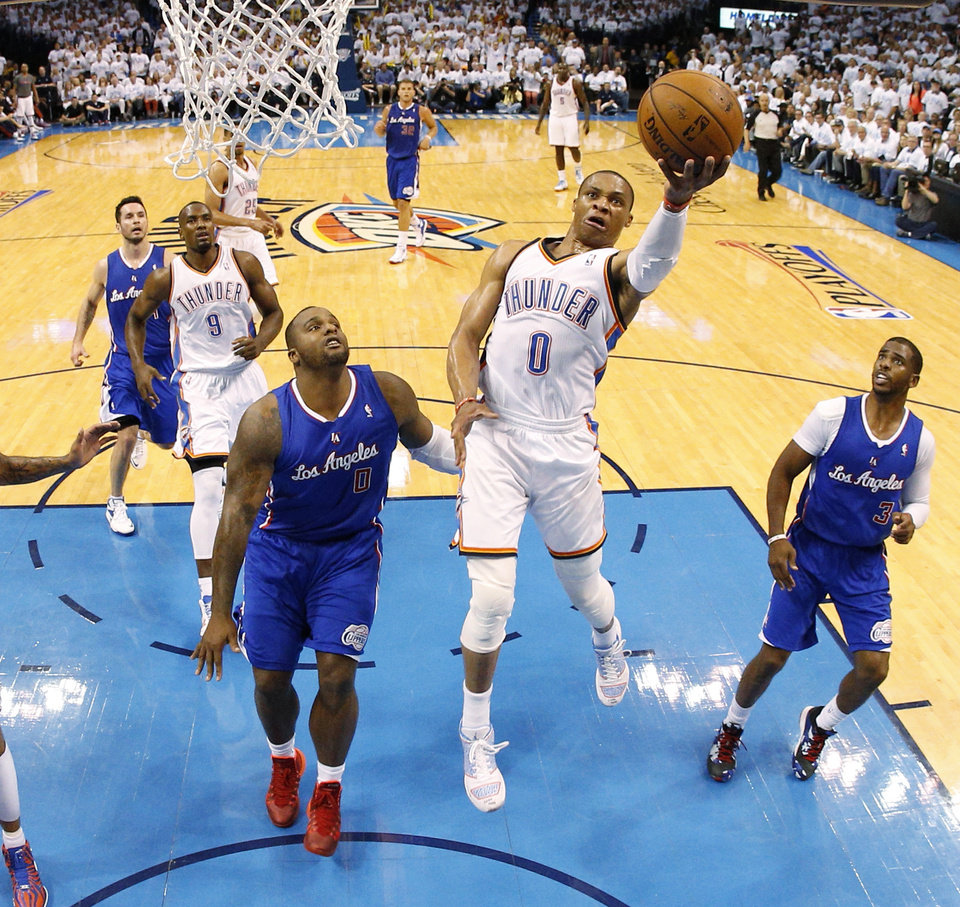 Photo - Oklahoma City's Russell Westbrook (0) goes to the basket between Los Angeles' Glen Davis (0) and Los Angeles' Chris Paul (3) during Game 5 of the Western Conference semifinals in the NBA playoffs between the Oklahoma City Thunder and the Los Angeles Clippers at Chesapeake Energy Arena in Oklahoma City, Tuesday, May 13, 2014. Photo by Bryan Terry, The Oklahoman