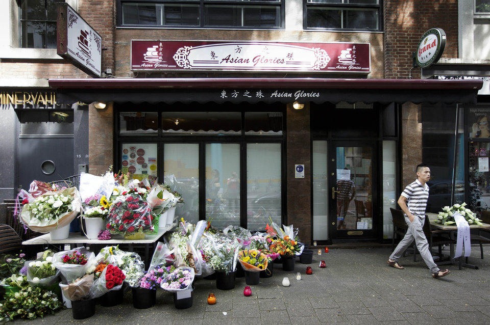 Photo - A man passes flowers placed in front of restaurant Asian Glories in Rotterdam, Saturday, July 19, 2014. Both owners, Jenny Loh and Popo Fan, were among those killed when a Malaysian jetliner was shot down over Ukraine Thursday. All passengers, 298 people from nearly a dozen nations, more than half being Dutch were killed. Malaysia Airlines said Saturday it has no immediate plans to fly the relatives of the 298 passengers and crew killed in the downing to visit the site in Ukraine because of security concerns. (AP Photo/Phil Nijhuis)