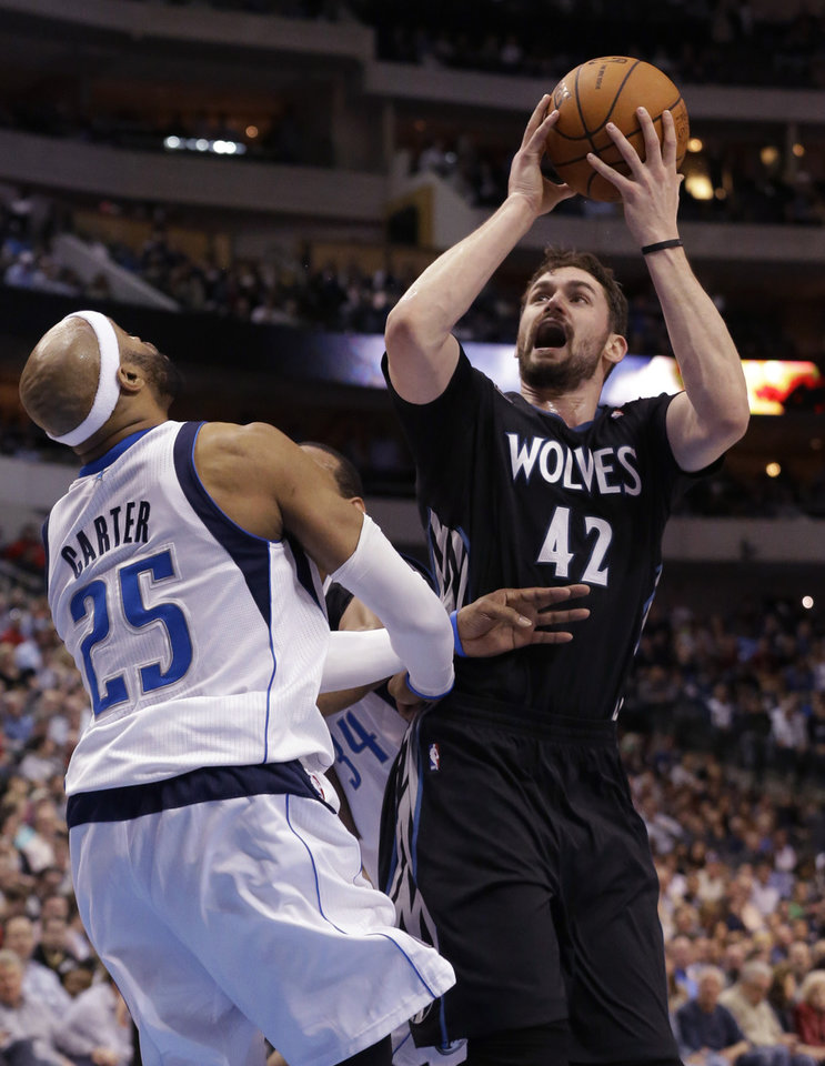 Photo - Minnesota Timberwolves forward Kevin Love (42) shoots against Dallas Mavericks guard Vince Carter (25) during the first half an NBA basketball game Wednesday, March 19, 2014, in Dallas. (AP Photo/LM Otero)