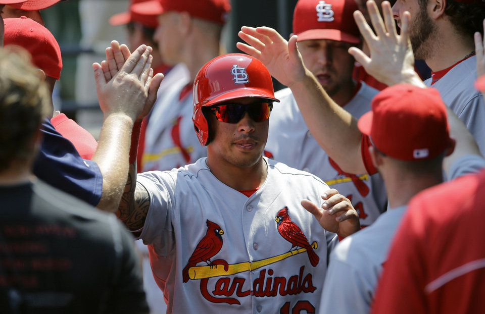 Photo - St. Louis Cardinals' Kolten Wong, center, high-fives teammates after scoring on a single by Jhonny Peralta in the first inning of an interleague baseball game against the Baltimore Orioles, Sunday, Aug. 10, 2014, in Baltimore. (AP Photo/Patrick Semansky)