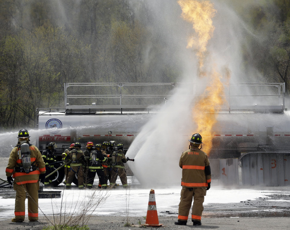 Photo - Firefighters spray fire suppressant foam to douse flames on a tanker truck in a simulated oil-spill fire during a drill on Wednesday, May 7, 2014, in Albany, N.Y. Firefighters are getting some practice battling crude oil fires as part of stepped-up efforts by the Cuomo administration to address safety threats from increased rail shipment of highly flammable crude from North Dakota to East Coast refineries. The Port of Albany has become a major hub for crude oil transport, with oil trains arriving daily on routes that cross the state from the west and north. (AP Photo/Mike Groll)