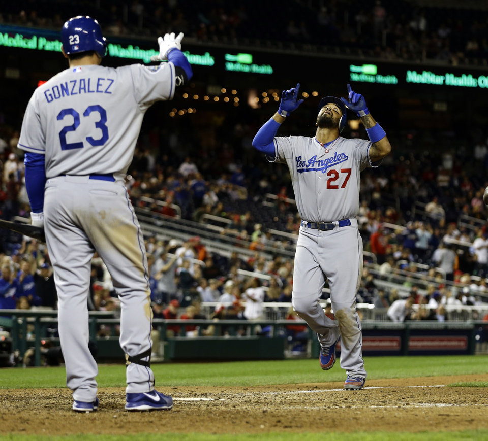Photo -   Los Angeles Dodgers' Matt Kemp (27) celebrates as he scores his solo home run, with Adrian Gonzalez (23), during the ninth inning of the second baseball game of a doubleheader against the Washington Nationals at Nationals Park, Wednesday, Sept. 19, 2012, in Washington. Kemp's homer was the game-winner and the Dodgers won the second game 7-6. (AP Photo/Alex Brandon)