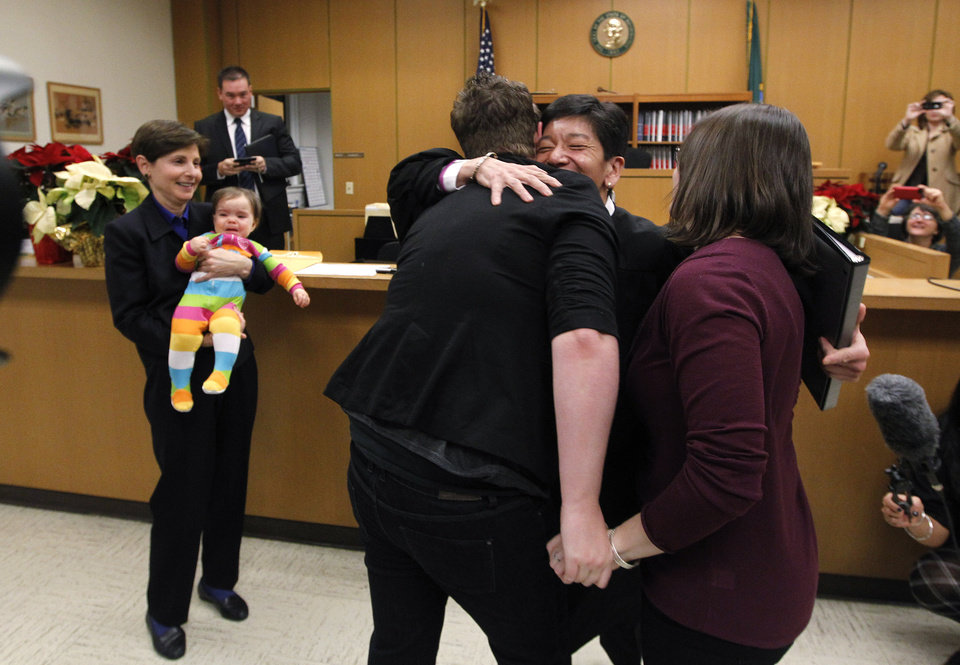 Judge Mary Yu, second right, embraces Emily Cofer, right, and Sarah Cofer after declaring them wed moments after midnight in the in the King County Courthouse, becoming among the first gay couples to legally wed Sunday, Dec. 9, 2012, in Seattle. At left, friend Anne Levinson holds the couple's daughter, Carter, nine months. Gov. Chris Gregoire signed a voter-approved law legalizing gay marriage Wednesday, Dec. 5 and weddings for gay and lesbian couples began in Washington on Sunday, following the three-day waiting period after marriage licenses were issued earlier in the week. (AP Photo/Elaine Thompson)