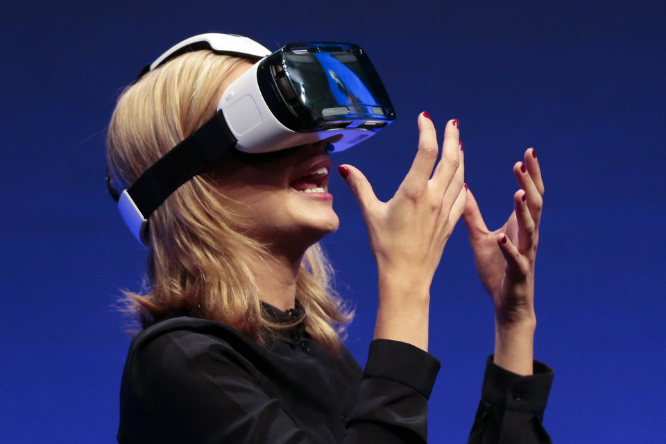 Photo - British television presenter Rachel Riley shows a virtual-reality headset called Gear VR during an unpacked event of Samsung ahead of the consumer electronic fair IFA in Berlin, Wednesday, Sept. 3, 2014. (AP Photo/Markus Schreiber)