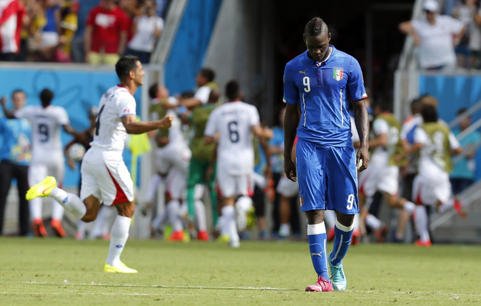Photo - Italy's Mario Balotelli walks away after Costa Rica's Bryan Ruiz scored the opening goal during the group D World Cup soccer match between Italy and Costa Rica at the Arena Pernambuco in Recife, Brazil, Friday, June 20, 2014.  (AP Photo/Frank Augstein)