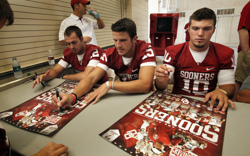 Photo - Quarterbacks Landry Jones, Drew Allen, and Blake Bell sign autographs during the Meet the Sooners event inside Gaylord Family/Oklahoma Memorial Stadium at the University of Oklahoma on Saturday, Aug. 4, 2012, in Norman, Okla.  Photo by Steve Sisney, The Oklahoman