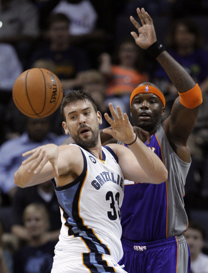 Memphis Grizzlies' Marc Gasol (33), of Spain, passes the ball away from Phoenix Suns' Jermaine O'Neal during the first half of an NBA basketball game in Memphis, Tenn., Tuesday, Dec. 4, 2012. (AP Photo/Danny Johnston)