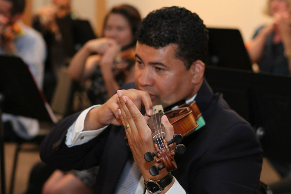 "Photo -  Guests can learn the basics of playing the violin in a relaxed setting at the Oklahoma City Philharmonic's ""Violins & Vino"" event Thursday. Photo provided"