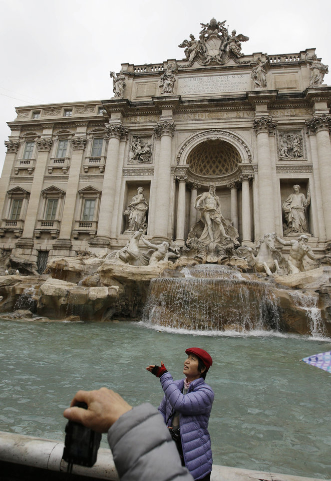 Photo - A tourist throws a coin into Trevi's fountain, in Rome, Monday, Jan. 28, 2013. The Fendi fashion house is financing an euro 2.12 million ($2.8 million) restoration of Trevi Fountain in Rome, famed as a setting for the film