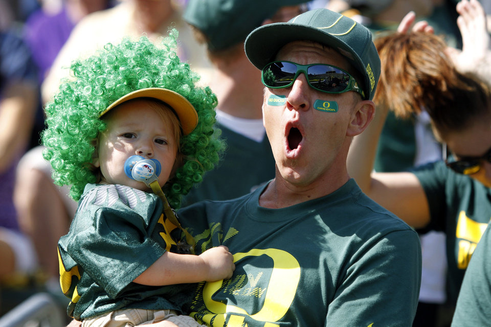 Photo -   An Oregon fan reacts while holding a child during the first half of their NCAA college football game against Tennessee Tech in Eugene, Ore., Saturday, Sept. 15, 2012.(AP Photo/Don Ryan)
