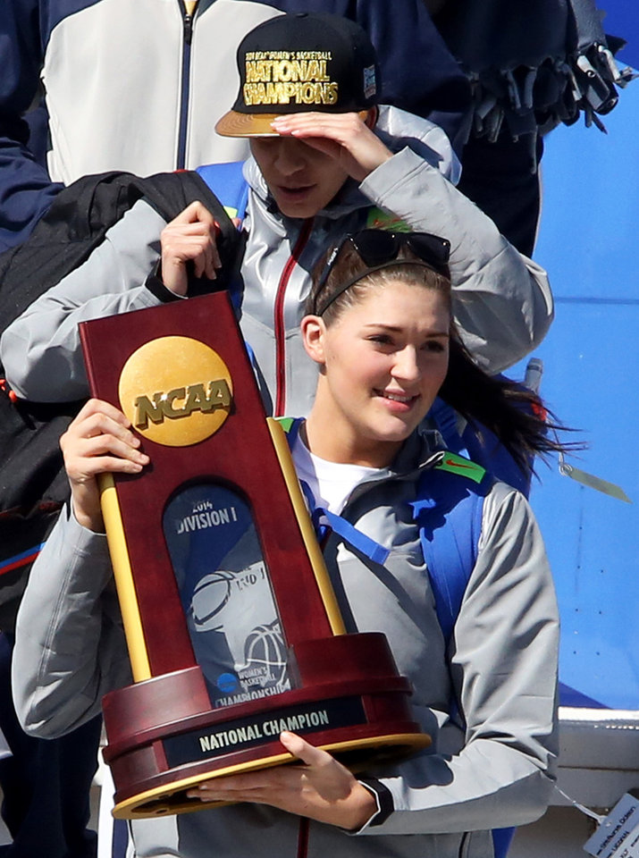 Photo - Connecticut's Stephanie Dolson holds the NCAA National Championship Trophy to fans as the team arrives at Bradley International Airport in Windsor Locks, Conn., Wednesday, April 9, 2014, the day after the Huskies defeated Notre Dame to clinch their ninth national championship. (AP Photo/Journal Inquirer, Jared Ramsdell)  MANDATORY CREDIT