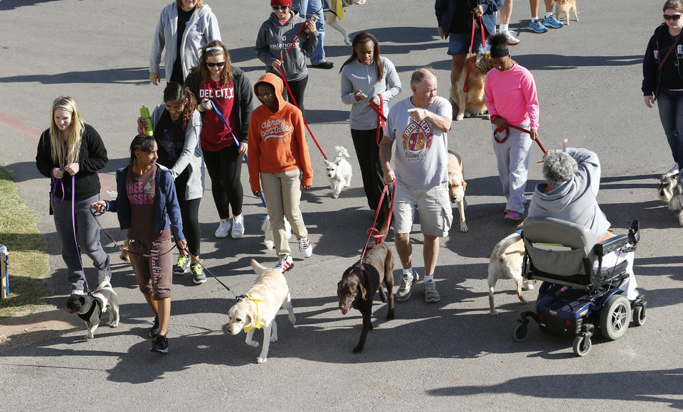 Photo - Walkers head out for a one-mile walk during DogFest Walk 'n' Roll Oklahoma City to benefit Canine Companions on Saturday. PHOTO BY STEVE SISNEY, THE OKLAHOMAN  STEVE SISNEY - THE OKLAHOMAN