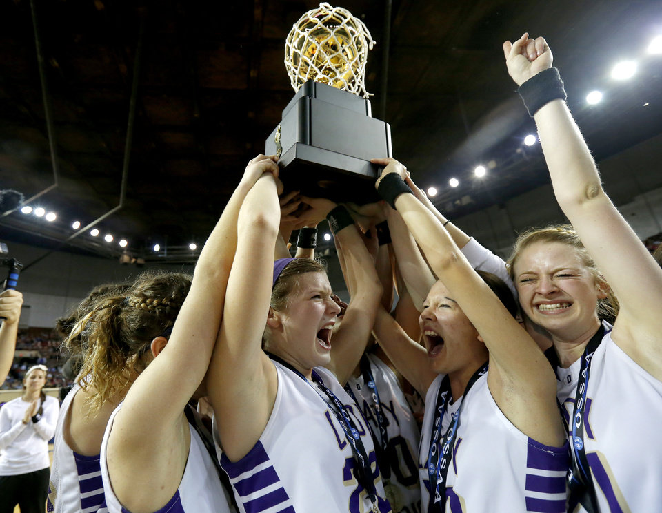 Photo - Okarche's Kenadey Grellner, center left, Chelsea Mueggenborg, and Randi Hufnagel, at right, celebrate with the trophy after winning the Class A girls state championship game between Okarche and Cheyenne/Reydon in the State Fair Arena at State Fair Park in Oklahoma City, Saturday, March 2, 2013. Photo by Bryan Terry, The Oklahoman