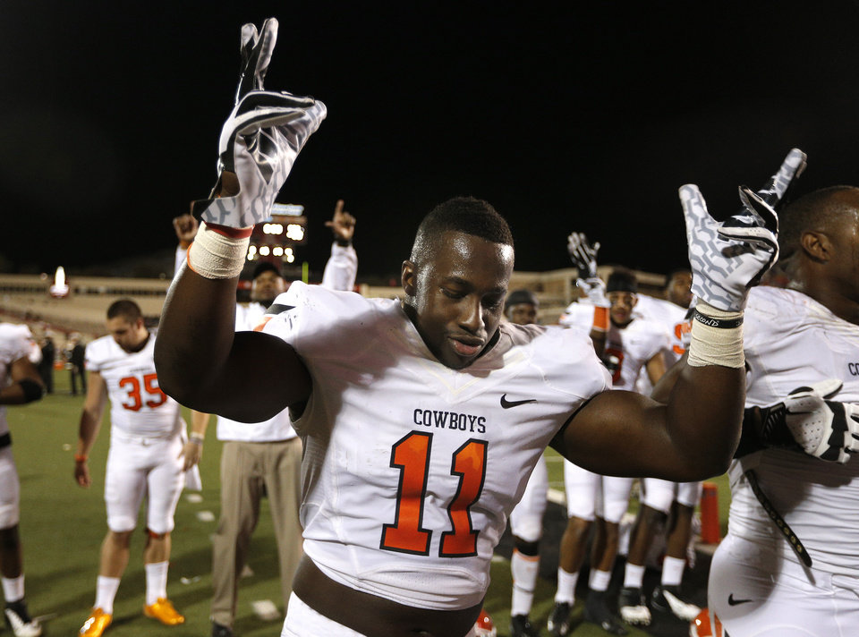 Oklahoma State \'s Shaun Lewis (11) celebrates the Cowboys win following the college football game between the Oklahoma State Cowboys (OSU) and the Texas Tech Red Raiders (TTU) at Jones AT&T Stadium in Lubbock, Texas, Saturday, Nov. 2, 2013. Photo by Sarah Phipps, The Oklahoman