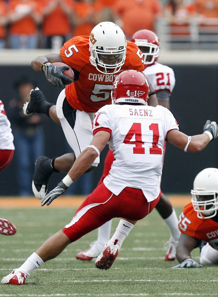 Photo - OSU's Keith Toston (5) leaps up in front of Houston's Nick Saenz (41) during the college football game between the University of Houston (UH) Cougars and the Oklahoma State University (OSU) Cowboys at Boone Pickens Stadium in Stillwater, Okla., Saturday, September 12, 2009. Photo by Sarah Phipps, The Oklahoman ORG XMIT: KOD