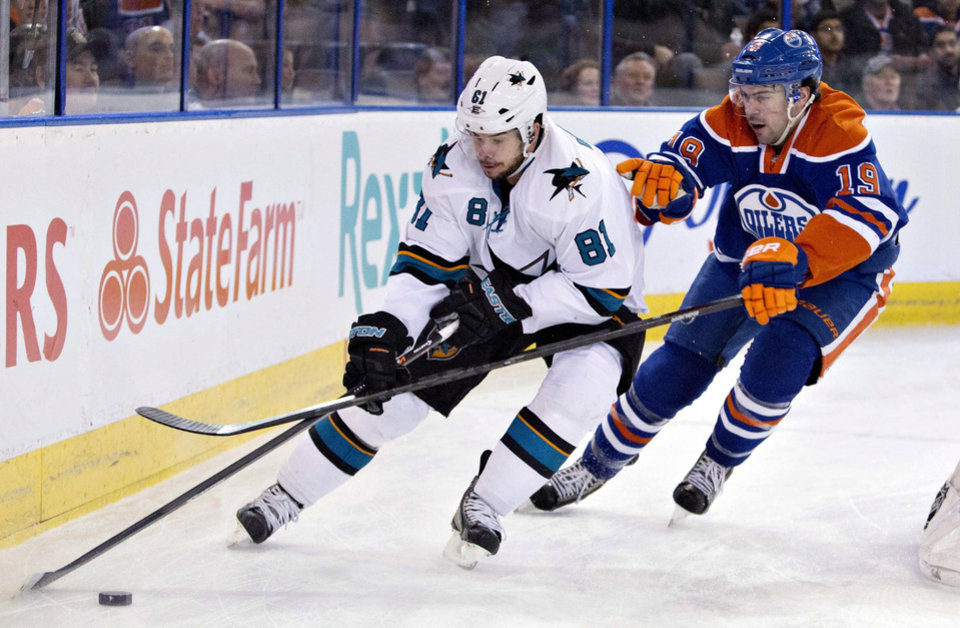 Photo - San Jose Sharks Tyler Kennedy (81) and Edmonton Oilers Justin Schultz (19) battle for the puck during the first period of an NHL hockey game in Edmonton, Alberta, on Wednesday, Jan. 29, 2014. (AP Photo/The Canadian Press, Jason Franson)