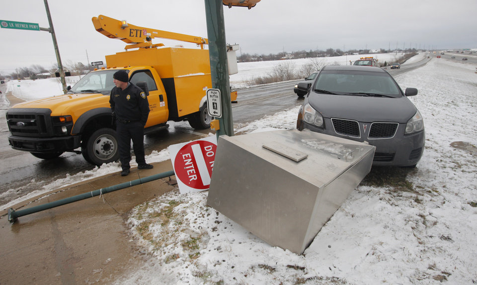 A driver lost control on the ice and snow and ran over the traffic signal control box at the end of the northbound exit ramp from the Lake Hefner Parkway at Hefner Road in Oklahoma City Monday, Feb. 13, 2012. The wreck resulted in long traffic delays at the intersections on Hefner Road when the lights stopped working. Photo by Paul B. Southerland, The Oklahoman