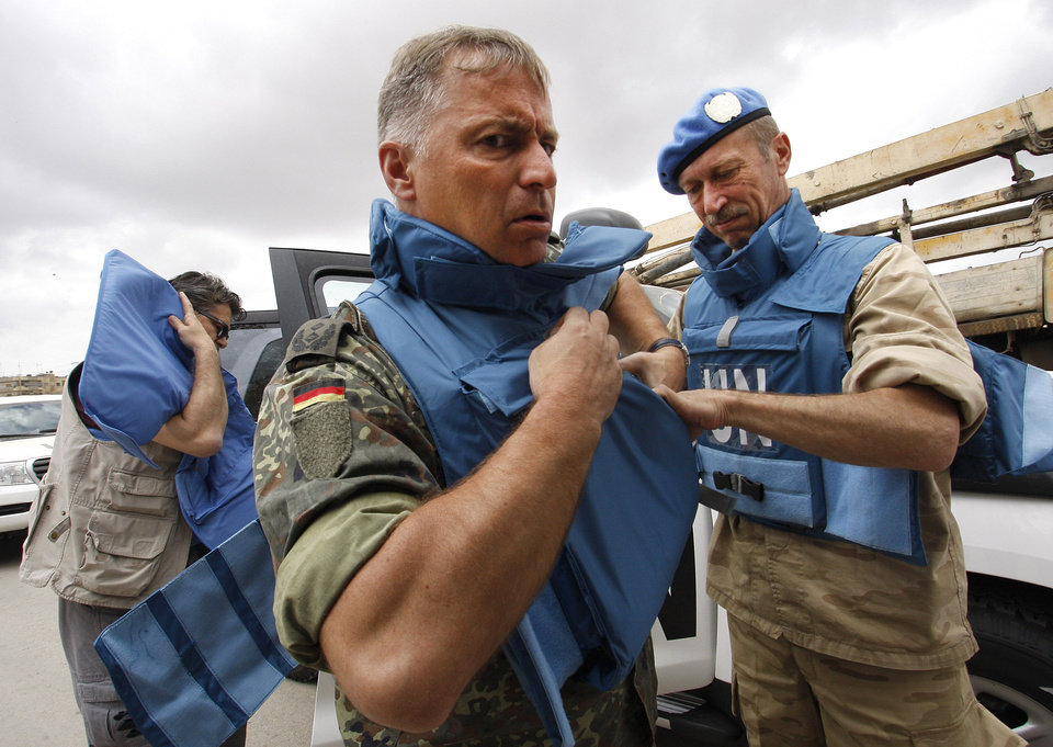 Photo -   In this picture taken during a UN observer-organized tour, UN observers don body armor upon their arrival in Hama city, central Syria, on Thursday May 3, 2012. Syrian security forces stormed dorms at a northwestern university to break up anti-government protests there, killing at least four students and wounding several others with tear gas and live ammunition, activists and opposition groups said Thursday. (AP Photo/Muzaffar Salman)